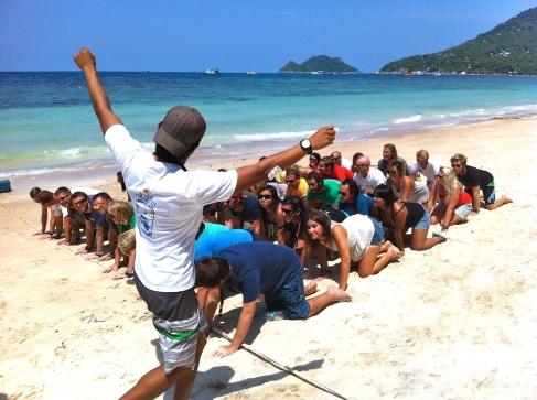 Underwater Human pyramid. On land practice Koh Tao, Thailand